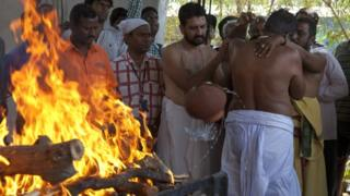 The victim's father, Madhusudhan Rao, performs rituals around his son's body