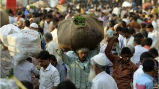 Man in a crowd carrying large package on his head in Mumbai