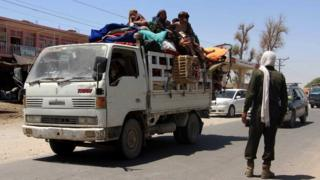 A family at a checkpoint in Helmand province, fleeing intense battles between government troops and the Taliban
