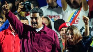 Venezuelan President Nicolas Maduro (L) gestures accompanied by his wife and first lady Cilia Flores after the National Electoral Council (CNE)