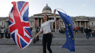 A Pro-European Union protester holds Union and European flags in Trafalgar Square
