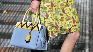 A model carrying a Prada bag