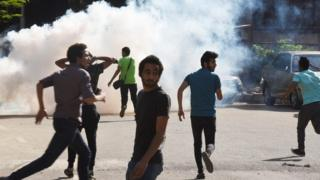Anti-government protesters run for cover as police fire tear gas in Cairo (25 April 2016)