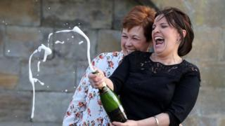 Paula Barraclough, left, and Lorraine Smith celebrate their Lotto win with a bottle of Champagne