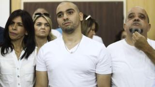 Israeli soldier Elor Azaria (C), who shot dead a wounded Palestinian assailant in March 2016, stands next to his mother Oshra (L) and father Charlie - 30 July 2017
