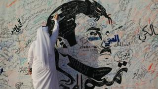 A man writes on a painting depicting Qatar's Emir Sheikh Tamim Bin Hamad Al-Thani in Doha, Qatar, 2 July 2017