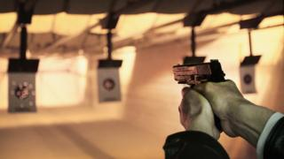A man shoots at a target at a shooting range during a class to qualify for a concealed carry permit, 14 February 2014