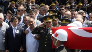 Turkey's Prime Minister Ahmet Davutoglu, left, holds the hand of the father of a Turkish soldier, Hamza Yildirim, at his funeral