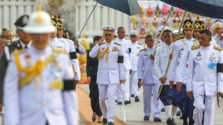 Thailand's King Maha Vajiralongkorn salutes as he leaves the monument of King Rama I after signing a new constitution in Bangkok