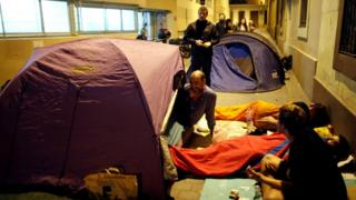 Parents camp out at the entrance of the occupied Reina Violant elementary school, one of the designated polling stations, the night before the banned October 1 independence referendum in Barcelona, Spain