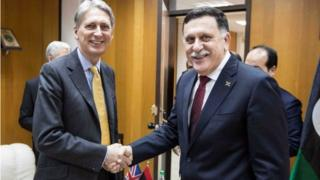 Philip Hammond shakes hands with Fayez al Sarraj