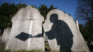 Gravestones with a shadow of a man on
