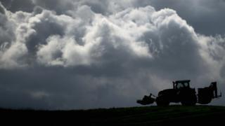 Трактор едет по полю на фоне тучи