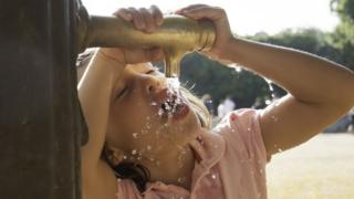 young girl drinking from a tap