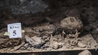 "A picture taken on May 13, 2017, shows a mummy lying in catacombs following its discovery in the Touna el-Gabal district of the Minya province, in central Egypt. Egyptian archaeologists have discovered 17 non-royal mummies in the desert catacombs, an ""unprecedented"" find for the area south of Cairo, the antiquities ministry announced. Along with the mummies, they found a golden sheet and two papyri in Demotic - an ancient Egyptian script - as well as a number of sarcophogi made of limestone and clay."