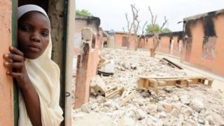 A female student stands in a burnt classroom at a school in Maiduguri, Nigeria, on 12 May 2012