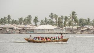 People crowd a small boat in Lagos