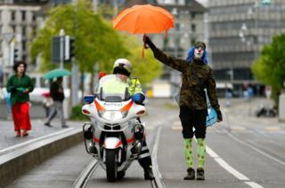 Un manifestante vestido de payaso cubre a un policía con su paraguas durante las protestas del 1 de Mayo en Zurich, Suiza.