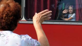 Женщина машет рукой своей семье, уезжающей в Россию из Донецка в июле 2014 года