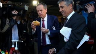 Bill Shorten takes a bite from a bun containing a sausage