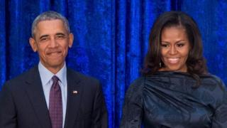 Barack and Michelle Obama stand beside each other smiling.