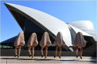 """Los miembros del elenco de la obra """"La nariz"""", de Dmitri Shostakovich, bailan disfrazados frente a la Ópera de Sídney, en Australia."""