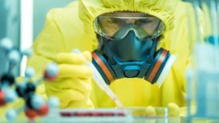 Un hombre con una máscara analizando una sustancia