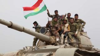 Kurdish forces sit on top of a tank waving the Kurdish flag after recapturing the town of Bashir on 1 May 2016