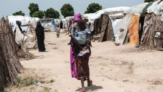 A woman carrying a child at her back walk through tents at the Muna makeshift camp for internally displaced people on the outskirts of Maiduguri, north-eastern Nigeria.