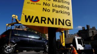 An illegally parked car is removed from a road next to Windsor Castle