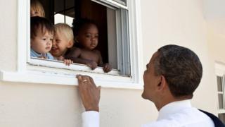 El expresidente de EE.UU., Barack Obama, sonríe a un grupo de niños en una guardería.