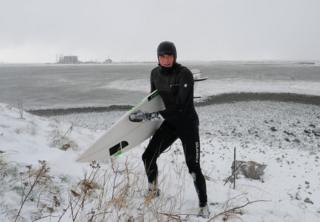 Surfer holding board walks up slope amid a snowy landscape