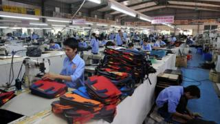 Employees of Ladoda company's leather factory, work on a production line in Van Lam district, northern province of Hung Yen on October 17, 2008