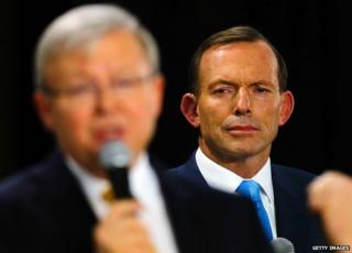 This picture taken on 21 August, 2013 shows Tony Abbott listening as Kevin Rudd speaks during a people's forum in Brisbane