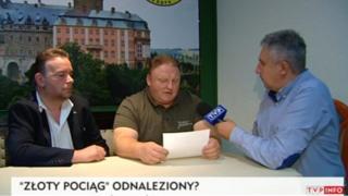 Andreas Richter, left, and Piotr Koper, centre, speak on Polish television