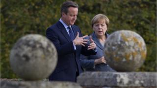 David Cameron and Angela Merkel in British Prime Minister David Cameron walks around the rose garden with German Chancellor Angela Merkel (R) during a meeting at Chequers, the Prime Minister's country residence on October 9, 2015 near Aylesbury, Buckinghamshire, United Kingdom