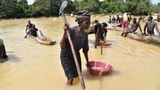 Gold prospectors work in the Pampana river on March 5, 2018 near Mekeni, northern Sierra Leone. Down a dirt road that slopes off a bridge, hundreds of men and women waist-deep in the river sift through gravel, separating specks of gold from the sludge. It may be the eve of a general election in Sierra Leone, but those who eke out a living here in Magburaka have few expectations from a new government, whichever party wins