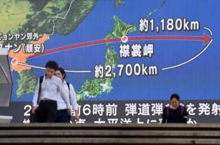 在东京街头,行人走过展示有日本和朝鲜半岛地图的巨大屏幕。