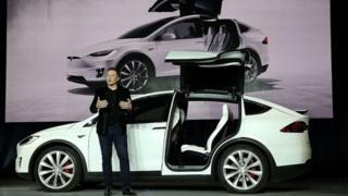 Elon Musk, delante de un coche blanco de Tesla