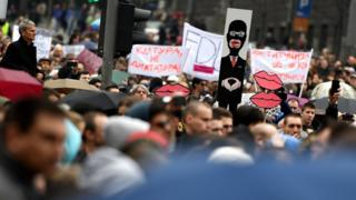 A protester holds a caricature of Aleksandar Vucic during an anti-government protest in Belgrade on 8 April