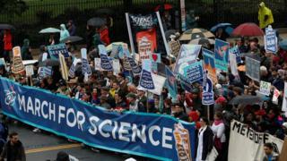 """科學家們舉著""""科學屬於大眾""""、""""科學不是沉默""""的標語在華府遊行。"""