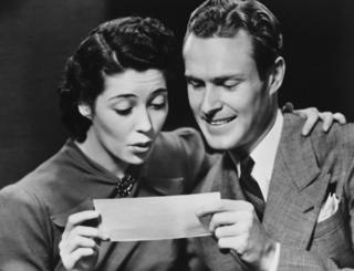Young couple reading telegram in studio. File photo