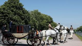 A carriage is pulled by four Windsor Grey horses from Windsor Castle during a dress rehearsal of the wedding of Prince Harry and Meghan Markle outside Windsor Castle on 17 May.