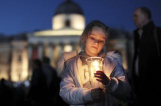 Niña sosteniendo una vela durante la vigilia en Trafalgar Square.