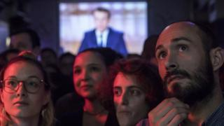 """Supporters of French presidential election candidate Emmanuel Macron for the """"En Marche!"""" movement (Onwards!) watch a live brodcast of the face-to-face televised debate between Emmanuel Macron and far-right Front National (FN) party candidate, Marine Le Pen in a bar in Paris, France, 03 May 2017."""