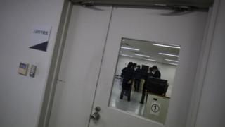 Guards seen through the window of a door at the East Japan Immigration Centre