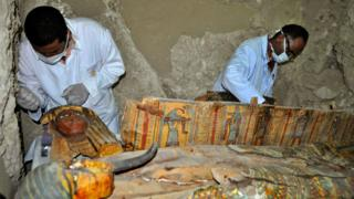 Two men in masks working on colourful coffins