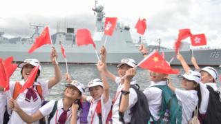 当局安排的学生代表在昂船洲海军基地迎接辽宁舰编队(中新社7/7/2017)