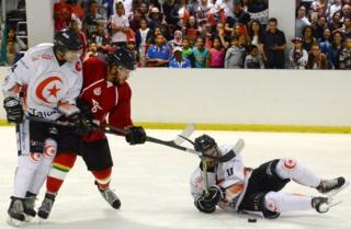 """Moroccan Capitals of rabat""""s player (red) vies with Tunisian Eagles de Carthage""""s player (white) during the """"African Ice Hockey Cup"""" on July 30, 2016 in Rabat"""
