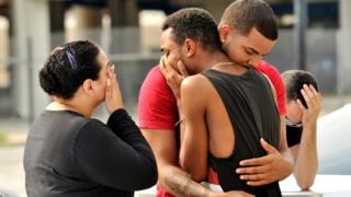 Friends and family members embrace outside the Orlando Police Headquarters during the investigation of a shooting at the Pulse night club, where as many as 20 people have been injured after a gunman opened fire, in Orlando, Florida, U.S June 12, 2016.